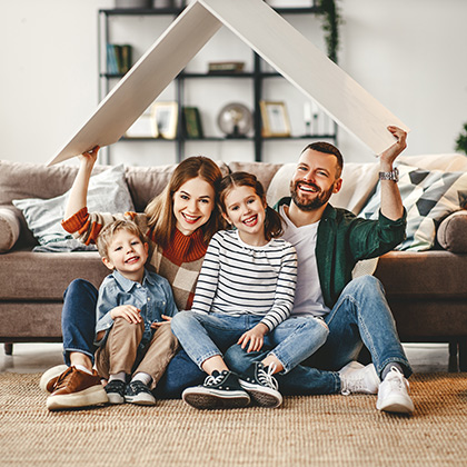 Family under cardboard roof in living room.