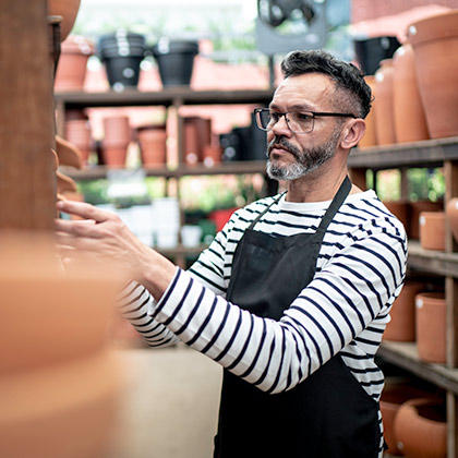 Business man working stacking pots on shelves.